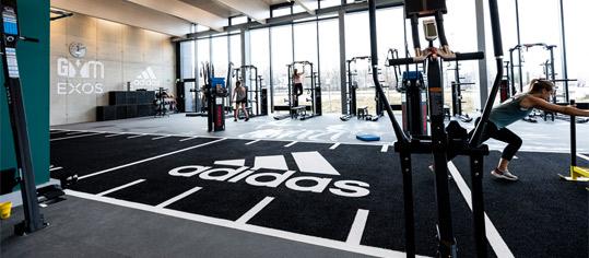 Gymnastik-Raum mit Adidas-Logo auf dem Boden.