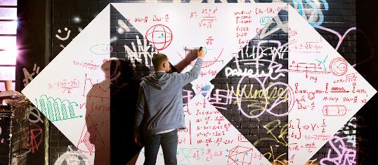 Mann malt Formeln auf eine Wand