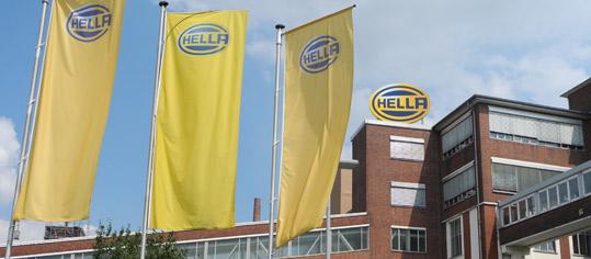 Fahnen der Firma Hella vor dem Unternehmenssitz.