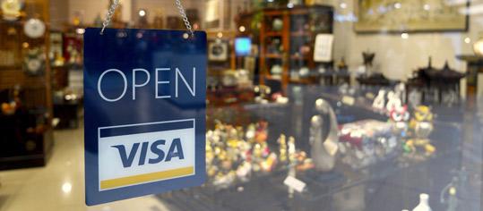 Eingangstür eines Geschäfts mit Schild der Firma Visa.