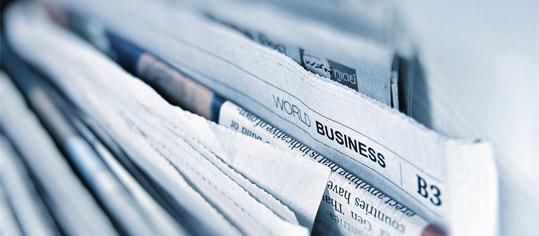 Finanzzeitungen in einer Ablage.