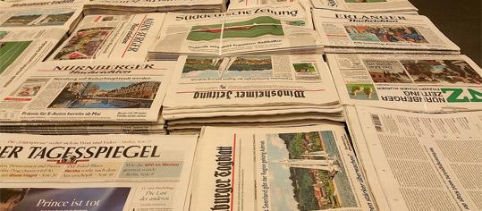 Verschiedene Tageszeitungen auf einem Tisch.