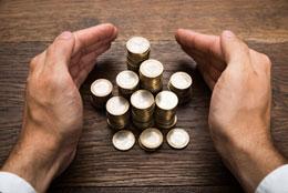 Zwei Hände schützen einen Geldstapel