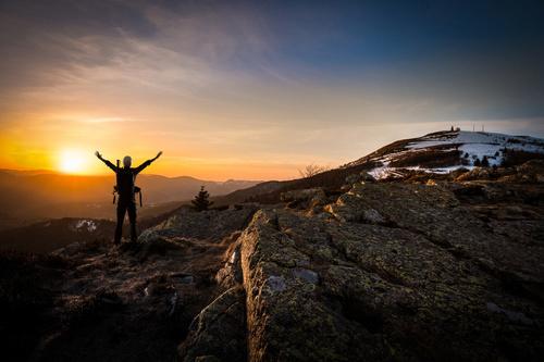 Bild zeigt Bergsteiger der auf einem Gipfelsteht